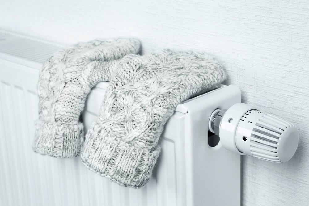 gloves on top of a wall mounted heater