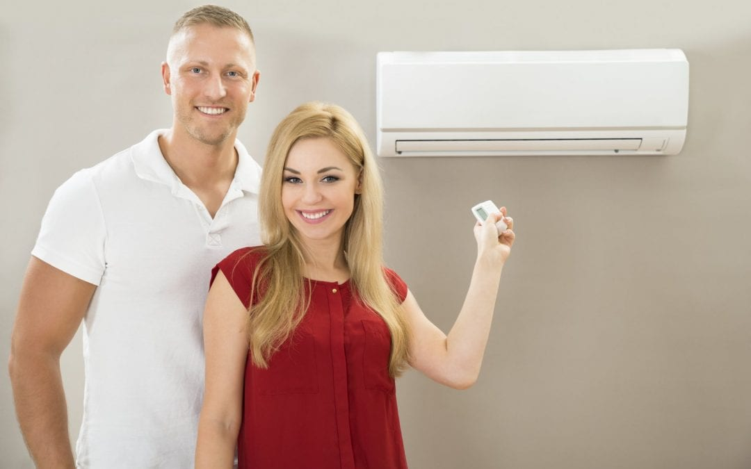 couple holding air conditioner remote